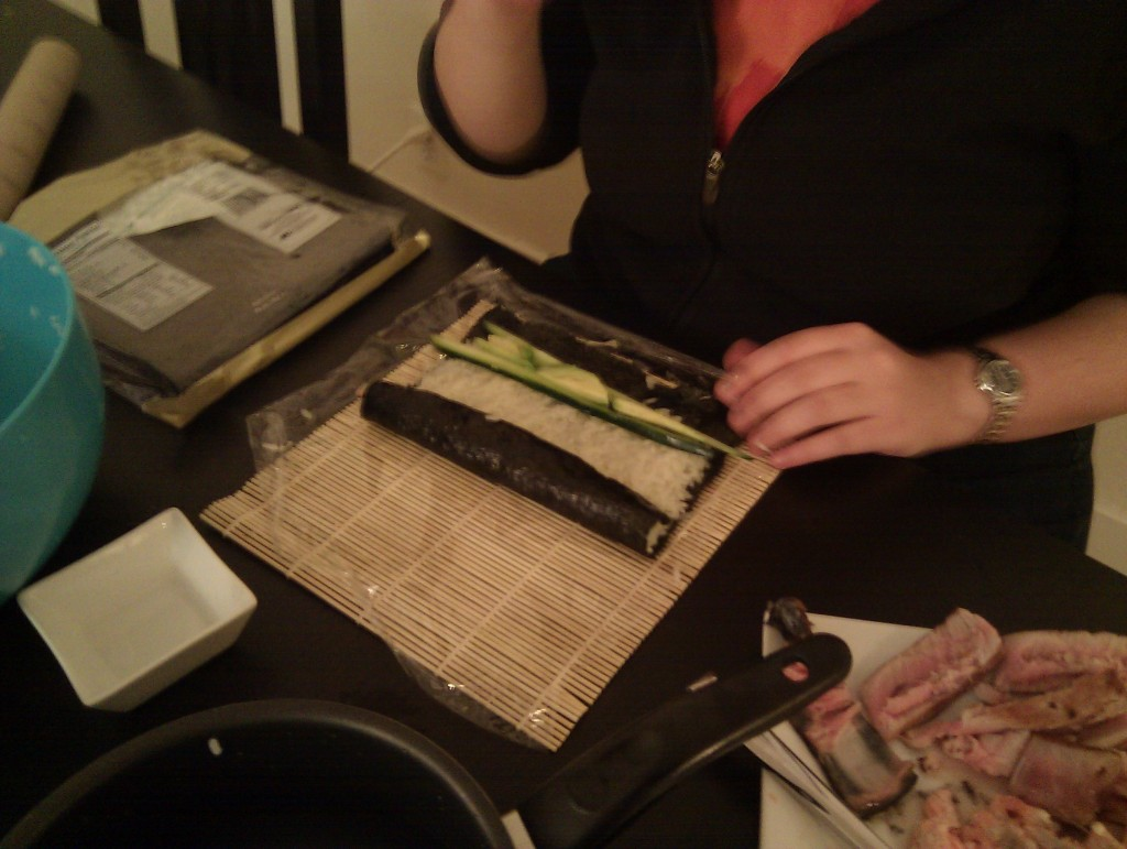 Rolling the sushi on the sushi mat. Using saran wrap made it way harder.